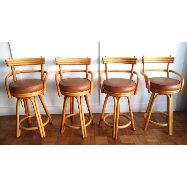 A set of 4 vintage bent rattan bar stools with swiveling seats. These need to be refinished and reupholstered. The finish...