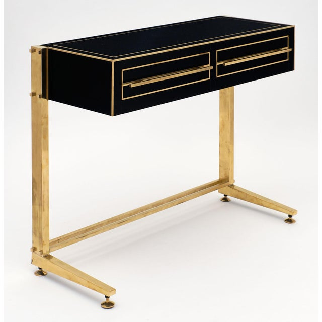 Spectacular pair of Murano glass covered console tables. We love the black glass and brass console table, a one of the...