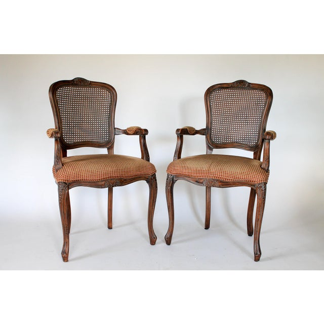 Pair of upholstered Fauteuils with caned backs and cabriolet legs. No makers mark. Some age wear to wood and fabric.