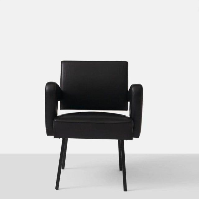 An armchair in black leather with cantilevered back by Jacques Adnet on an enameled steel base.