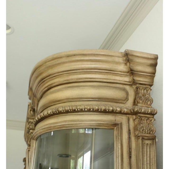 A large exquisite Baroque style china cabinet with touch activated lighting. This cream finished piece has a beveled...