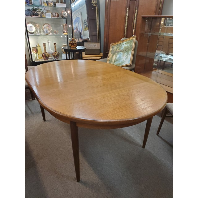 """Mid century modern teak oval table with a pop up leaf that is stored inside, by G-Plan. 64"""" W 44"""" D 29"""" H 18"""" Leaf"""