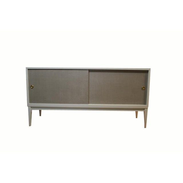 M|n Originals lacquered console on solid maple tapered leg frame with natural linen doors which have been colored and...