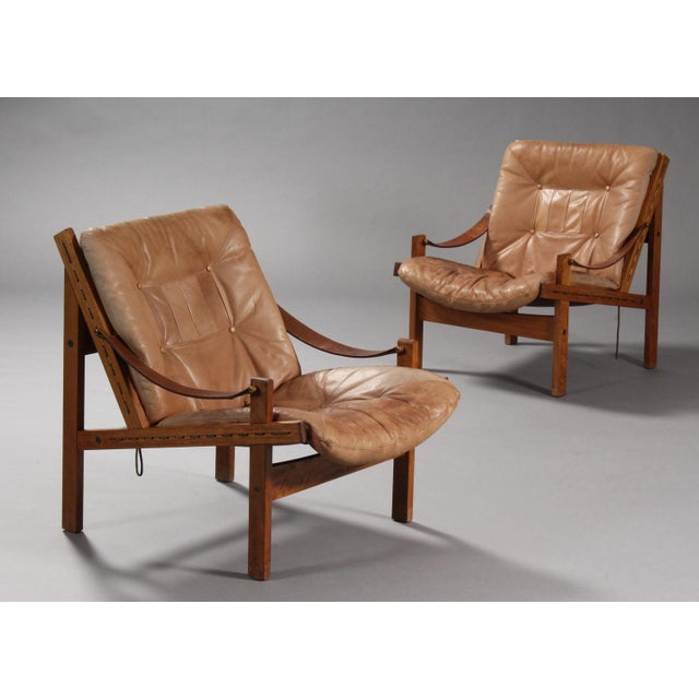 Thorbjørn Afdal, Norwegian designer. Pair of easy armchairs with solid walnut wood frame, loose cushions upholstered brown...