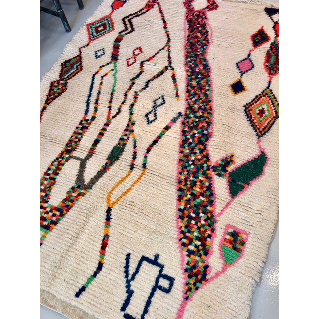 This rug was handmade in Morocco out of wool with a multicolored pattern on it. It is a very quality rug and adds a pop of...