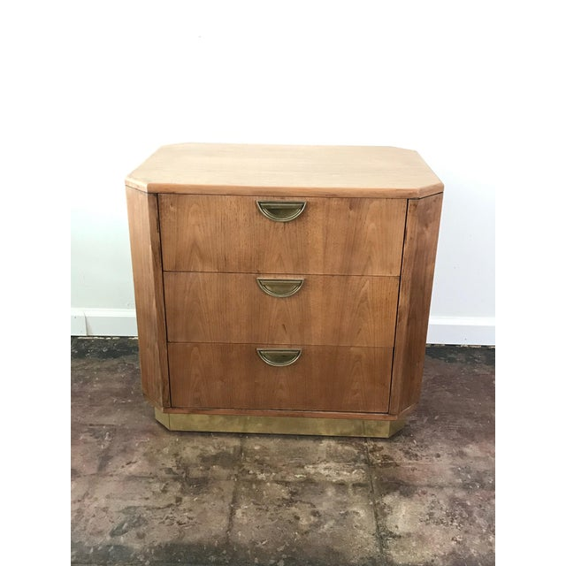 Oak campaign style night stand with three drawers and gold plated chrome detailing at the bottom. Classic campaign style...