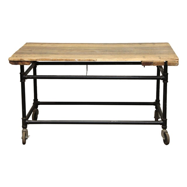 This is a wooden work table with black metal legs and wheels. The piece is worn from use.