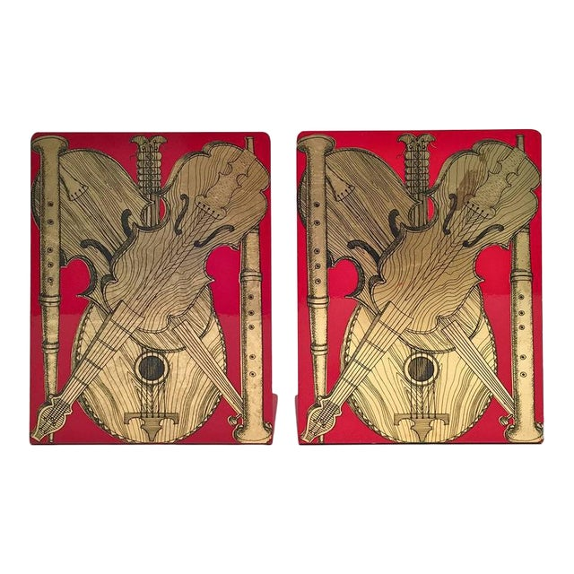 Fornasetti Strumenti Musicali music metal bookends. Atelier Fornasetti. The L-shaped bookends are decorated with a red-...