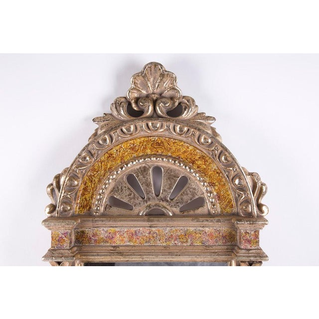 The ornate light-gold tone painted plaster and wood wall mirror features a classically inspired pediment and twisted...