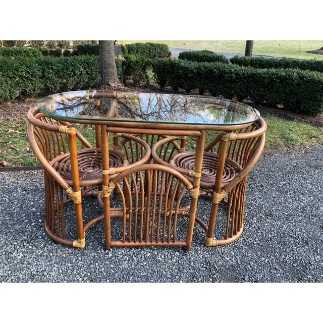 Mid-century bentwood and rattan dining set with glass top. Matching chairs have seats with concentric circles. The...