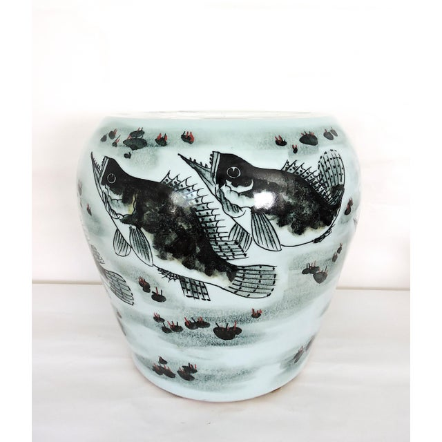 Heavy round ceramic drum stool or garden seat hand painted with large fish on the sides and top swimming amongst green...