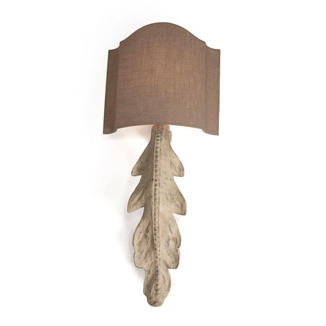 Wooden leaf wall sconce with beige shade.