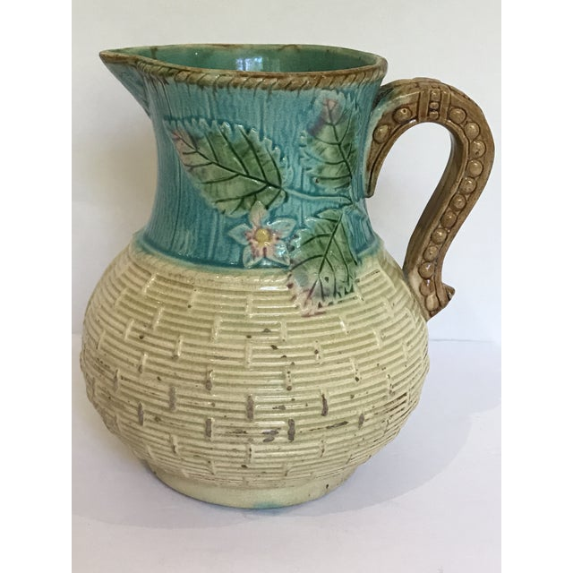 Charming Majolica basket weave designed pitcher with lovely strawberry blossoms near handle.