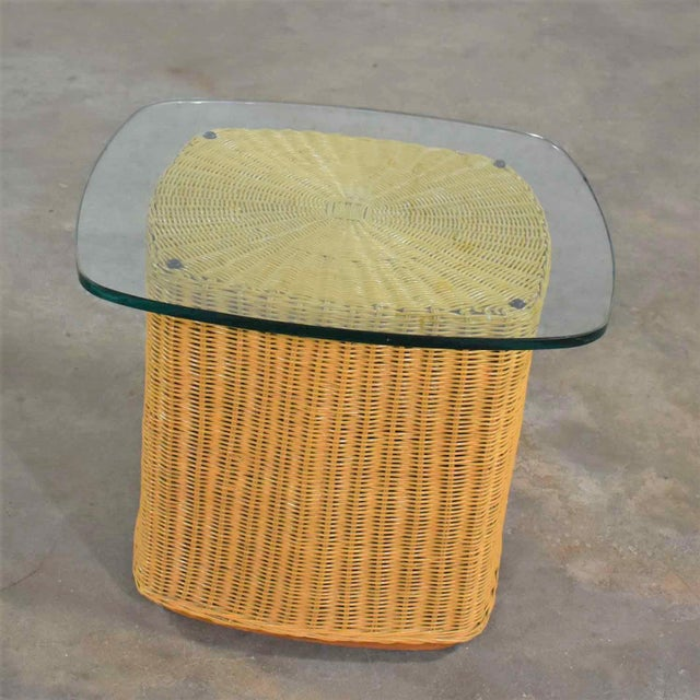 Handsome organic modern rattan wicker side table or end table having a ½ inch thick glass top with an overhang. It is in...