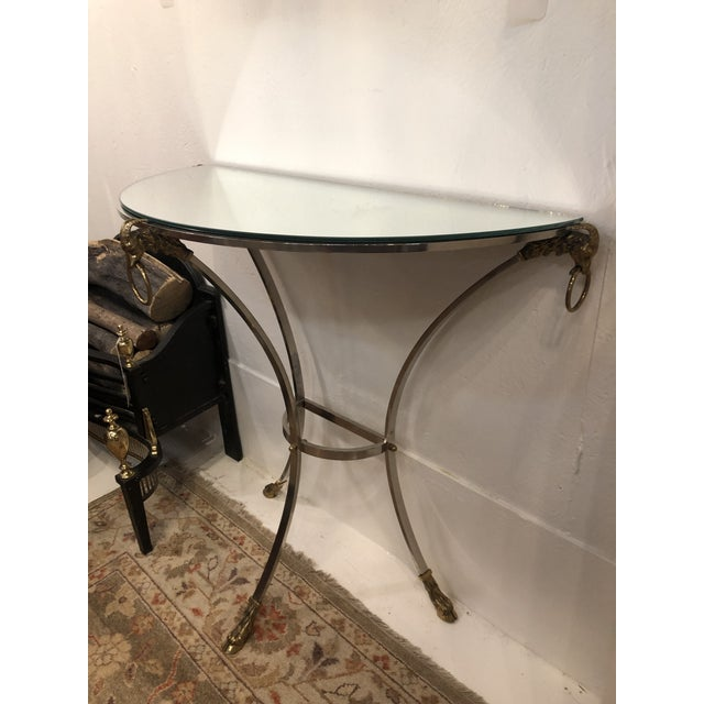 Polished steel mirror top Demi-lune console with brass rams heads and hooded feet. As the first sign of the Zodiac, Aries...