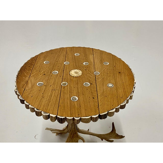 Chic and rare organic modern side table having tripod shaped legs artfully crafted from authentic antlers. The top has...