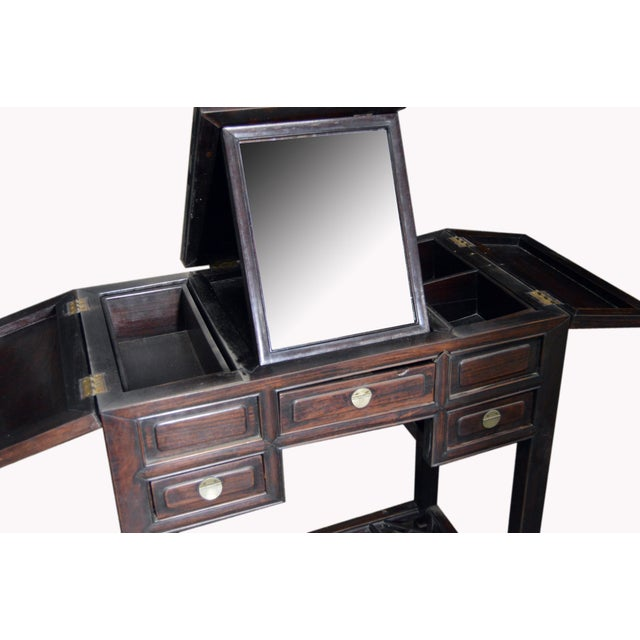 A vintage Chinese lacquered wood dressing table with stand up mirror and drawers from the first half of the 20th century....