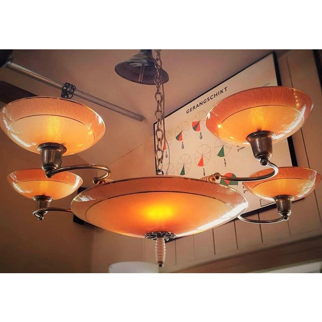 Unusual eight-light salmon or apricot colored chandelier with textured glass and gold accents. From France, circa 1940....