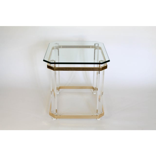 Hollywood Regency brass and Lucite side table in the manner of Charles Hollis Jones. No maker's mark. Light scratches to...