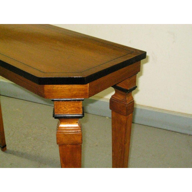A pair custom walnut consoles in the neoclassical manner on tapered legs with ebonized banding.
