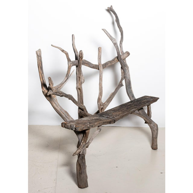 Early 20th century estate made garden or outdoor bench. The piece is composed of driftwood and reclaimed floor planks in a...