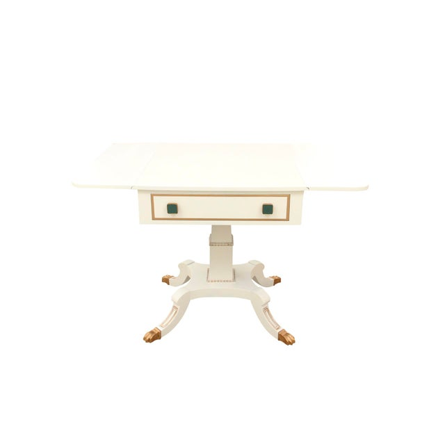 Neoclassical drop leaf side table featuring blue knobs and gold detailing. The table is of wood construction with a fine...