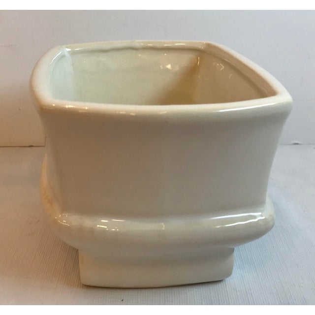 Beautiful cream colored footed planter with classic design features.