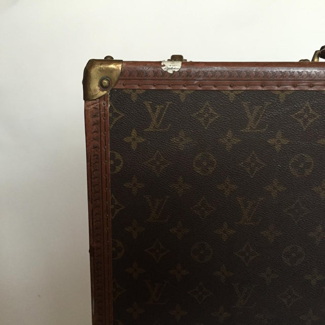 This Louis Vuitton Alzer 65 hard sided trunk Suitcase with interior tray, in monogram canvas with travel stickers from...