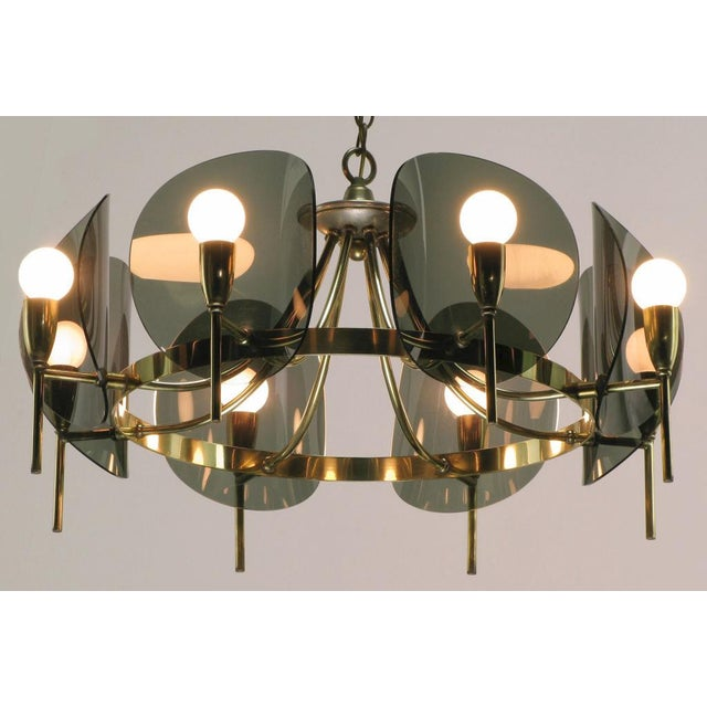 Round eight arm chandelier in brass, with smoked bent acrylic reflectors. With three feet of chain and canopy.