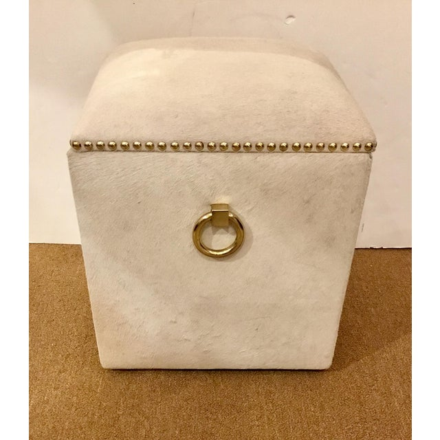 Stylish, modern, contemporary Arteriors Harrison Hide Stool, upholstered in white hide with brass Accents, storage covered...