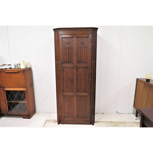 This is a lovely English tiger oak wardrobe. The front features a nice linen fold design. Inside is a bar for hanging...