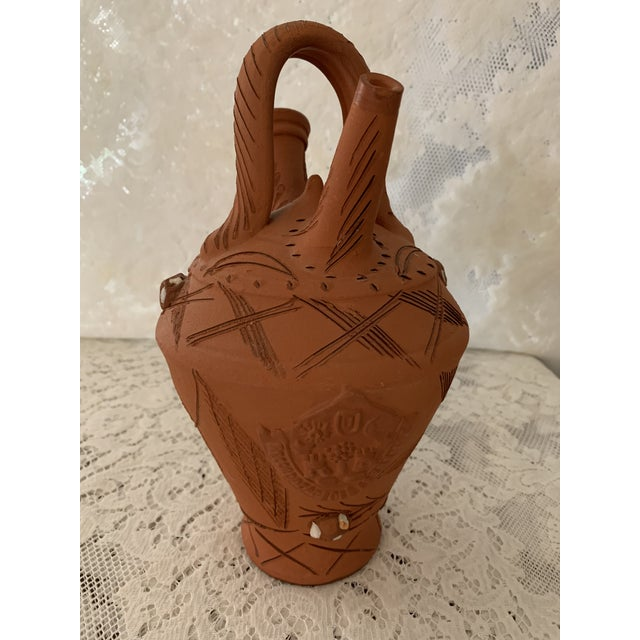 "Handmade in Portugal. Unglazed terra cotta pottery. Embedded quartz chips. Handle, 2 spouts, carved designs. 10"" high; 6""..."