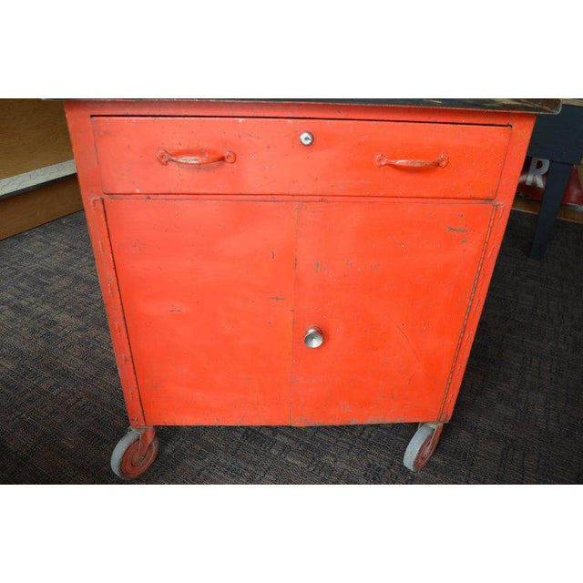 Storage cabinet on wheels of sizzling red-orange paint with steel top. Highly functional as kitchen island, home bar or...