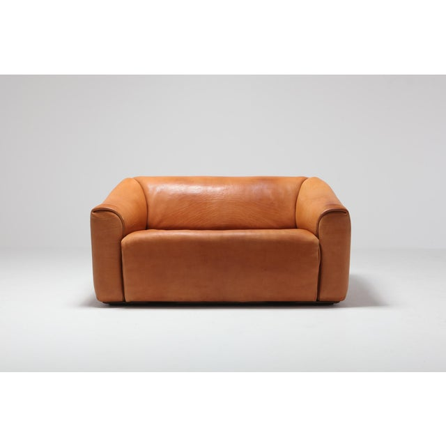 Cognac leather two-seat sofa by Swiss manufacturer De Sede. Bullhide leather with retractable seating for an even more...