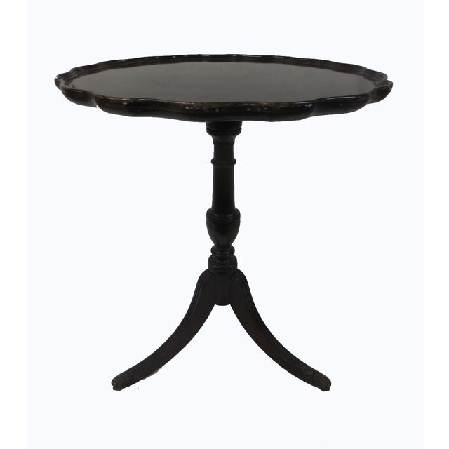 "A mahogany piecrust table, marked ""Brandt Furniture of Character."" One brass claw-shaped cap is missing. Some wear,..."