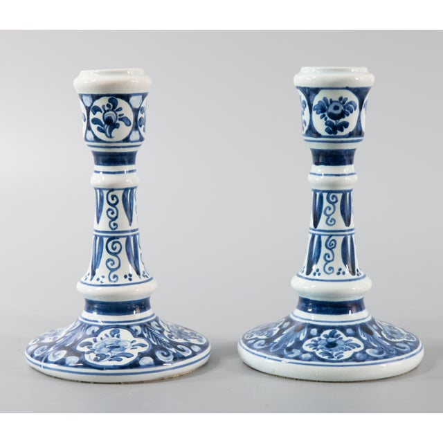 A lovely pair of Mid-Century Dutch Delft faience candlesticks. These fine candlesticks are hand painted with a floral...