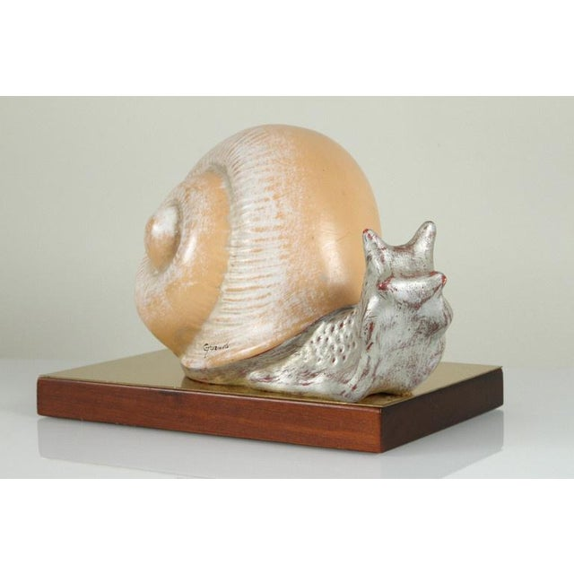 This is a hand-painted Italian ceramic snail sculpture mounted on base of brass and wood. The piece was made in the 1970s...