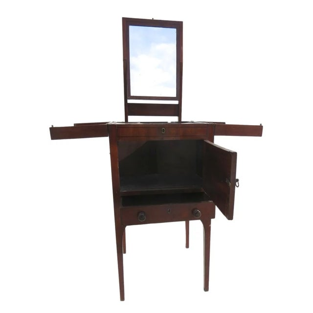 English mahogany enclosed lift top dressing stand. Oval inlaid door, one drawer. Lift out mirror with hinged mechanism....