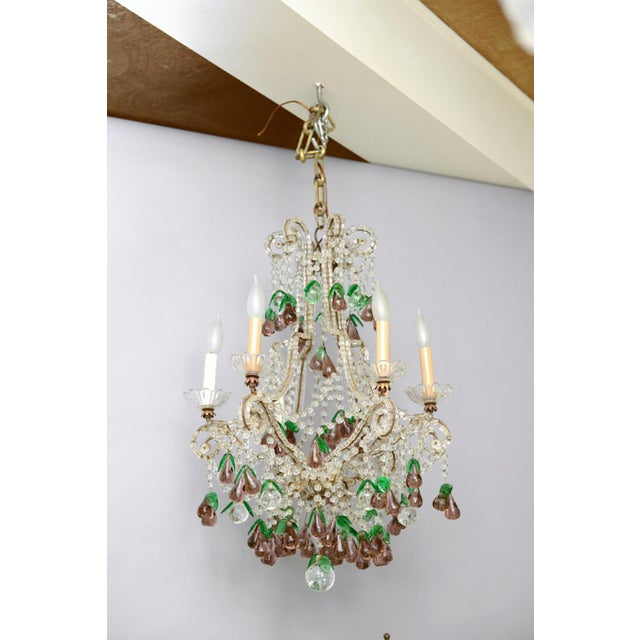 Chandelier, in the Italian Maria Theresa style, having a cage-form frame of gilded iron, entirely affixed with cylindrical...