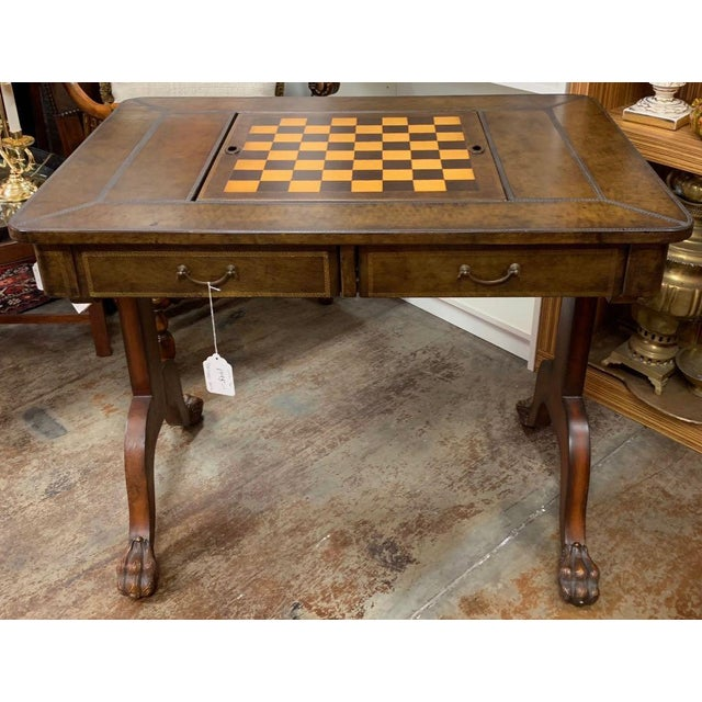 Maitland-Smith leather top game table with mahogany legs and hairy paw feet. The upper part of the table, including the...