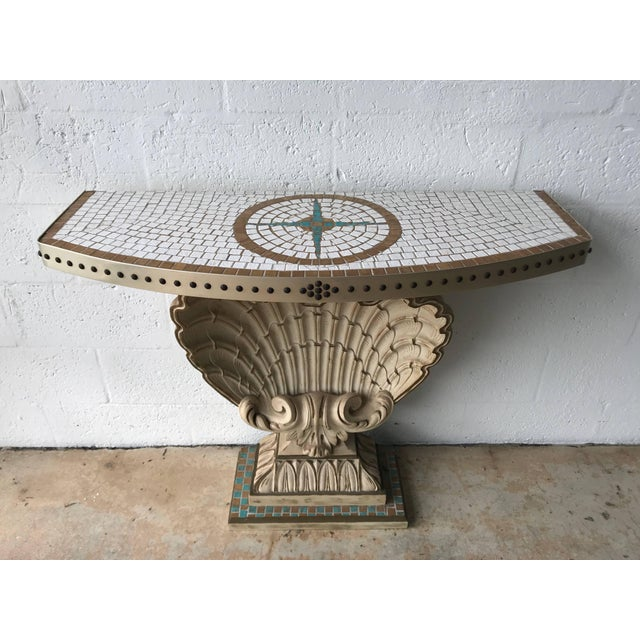 Hollywood Regency carved shell demi-lune console by Maison Jansen, with gilt carved wood, and a ceramic tiled top wrapped...