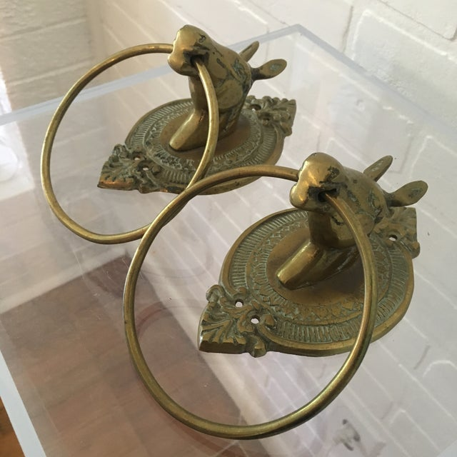 "Pair of vintage horse towel rings in brass. Minor wear and patina consistent with age. Each hook measures 4.25"" wide and..."