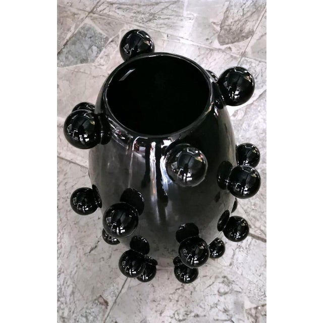 Particular polished black ceramic vase; it was made by a company in Northern Italy with a completely manual process...