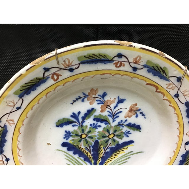 18th century Dutch delft polychromed plate. The plate is very vibrant with multi colors and decorated with foliage/...