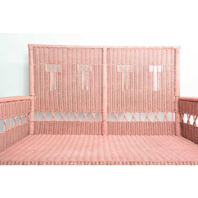 This painted pink rattan settee has an attractive and intricate pattern and design overall, especially on the back seat of...