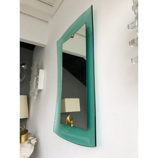 Rare wall mirror in blue turquoise green curve glass, brass elements by the famous crystal and glass manufacture Cristal...