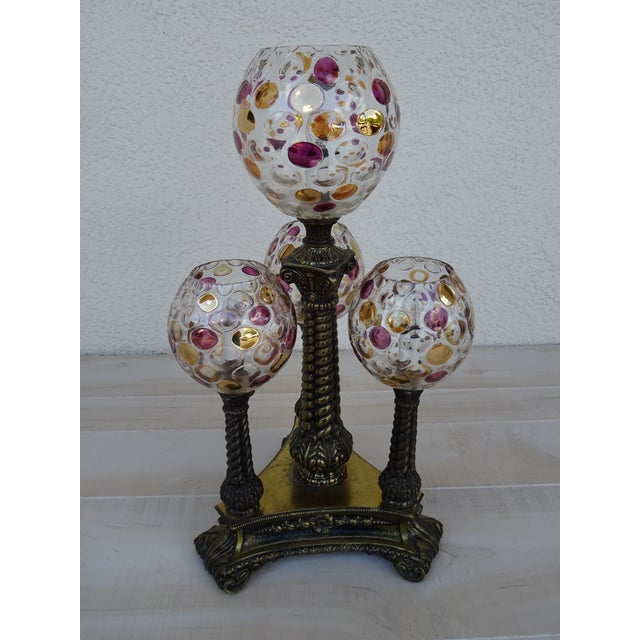 A vintage L&L WMC lamp with four polka dotted glass globes sitting on ornate brass columns in a triangular shape. It has a...