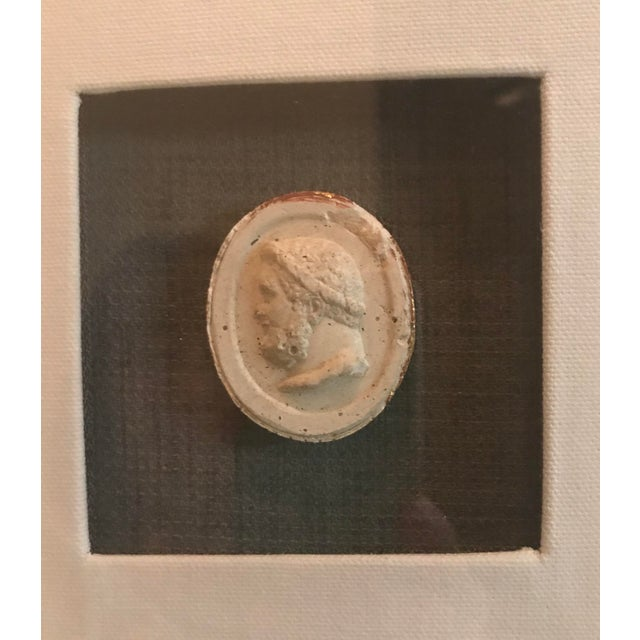 """2"""" plaster intaglio has gold leafed edges mounted on dark gray fabric, centered in a white fabric covered mat. Wood frame..."""