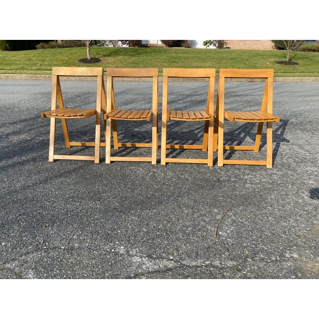Four Maple folding chairs with slat seat made in Romania. Great condition. Slim profile makes them easy to store and bring...