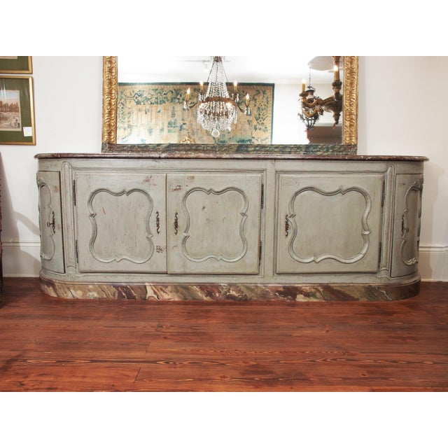 A five door, polychrome marble top enfilade with raised, paneled doors, the doors on each end curved, all opening to...